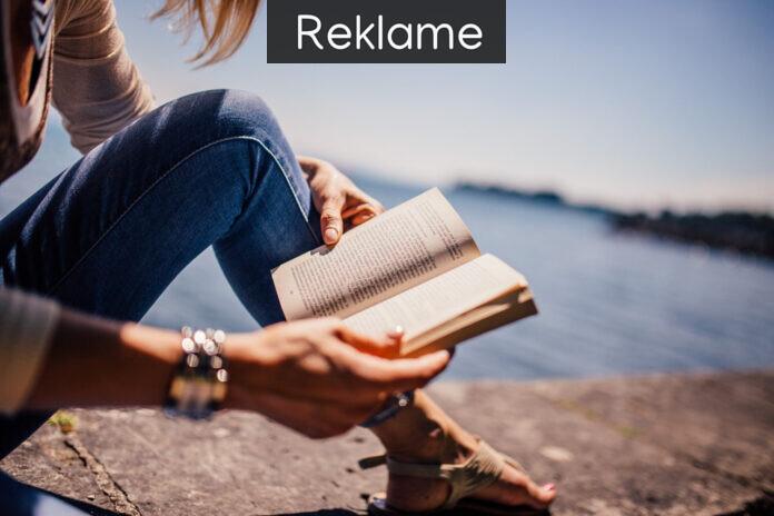 Kvinde læser ved en sø.